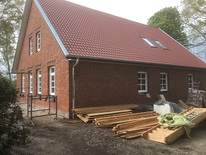 Haus mit Holz im Vordergrund